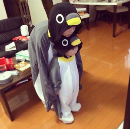 日本一对可爱兄弟身穿国王企鹅的全套服装,站在电视机前面看著80年级