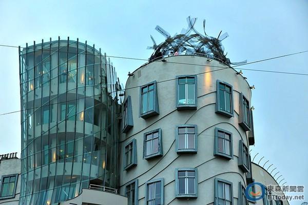COSMOS總代理大腳旅行社指出,布拉格「跳舞的房子」是其暱稱,此屋本是荷蘭國民人壽保險公司大樓,又有另一名稱為「弗萊德與琴吉的房子」,取自美國著名的踢踏舞蹈家名字,由加拿大的前衛設計師法蘭克·蓋瑞,與捷克建築師弗拉多·米盧尼克共同設計,1992年著手設計,1996年完工,從此後便成為布拉格著名的觀光景點之一。 跳舞的房子外觀非常奇妙,扭扭擺擺模樣,又好似一人靠在另一人身上。外觀由兩棟房子結合的「跳舞的房子」,據當地人說,左側有腰身的房屋其實是指女性舞蹈家琴吉,斜斜靠在右側舞
