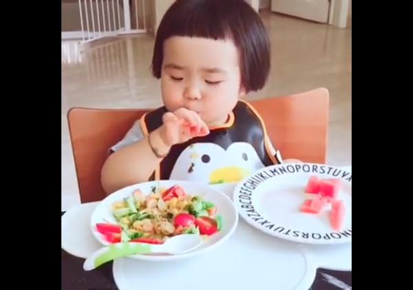 短劉海小萌娃不挑食把食物吃光光。(圖/翻攝自美拍/段语duanyu,下同) 網搜小組/綜合報導 美拍用戶「段语duanyu」日前分享一段影片,1名短髮小女娃不停地將桌面上的食物抓到嘴裡吃,一下拿西瓜,一下拿沙拉,不出多久就將盤子「清光光」,可愛的吃貨模樣讓網友直呼,「長得好像『手機女孩MiM』貼圖!」  直接端起盤子吃。 影片中,只見小吃貨穿著圍兜兜,面前擺著2個大盤子,1盤裝西瓜,另1盤裝玉米、番茄和小黃瓜,她則左右手並用,俐落地將食物放進嘴哩,期間還有人拿湯餵她。沒過多久,食物都被掃光,更厲害的是