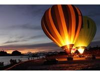 台東縣政府辦理的熱氣球嘉年華第二場光雕音樂會,於成功鎮三仙台舉行,熱氣球與曙光及升起的日出相輝映,讓觀眾驚呼連連。(圖/台東縣政府提供)