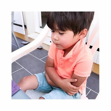 ▲阿弟抱著手臂、一臉悶悶不樂地坐在椅子上。(圖/翻攝自王君萍臉書)