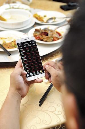 全職投資人的生活不像外界想得輕鬆,權證小哥連吃飯都不忘緊盯盤勢。