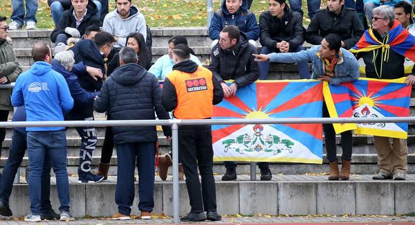 因为发现观众席上挂著西藏旗帜「雪山狮子旗」,使他们愤而离场.