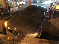 ▲▼板橋男子酒後開BMW轎車撞進公園,被警方上銬送醫。(圖/記者趙永博攝)