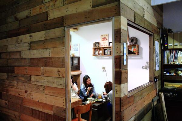 室内有间小木屋隔间,只有两,三张桌,可见后方开放式厨房的木质吧台区.