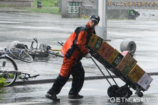 颱風天送貨員在風雨中蹣跚前進。(圖/記者陳明仁攝)