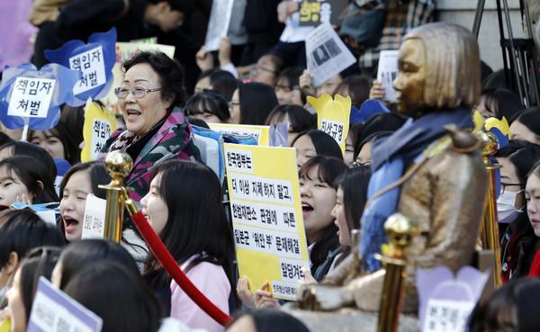 韓國慰安婦與大學生在日本駐韓大使館附近抗議,要日本政府對慰安婦做出賠償並道歉。一旁的雕像就是象徵著慰安婦。(圖/達志影像/美聯社)