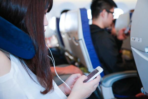 飛機上使用3c產品,飛機上滑手機,飛機上玩手機,飛機上聽音樂,戴耳機(圖/記者林世文攝)