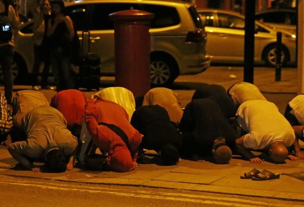 ▲▼倫敦民眾在發生駕車攻擊的清真寺附近為傷者進行祈禱。(圖/路透社)。(圖/路透社)