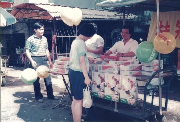 1988年,王正明(左1)帶著公司員工在菜市場推廣桂冠水餃,標榜買3盒送1顆海灘球。(桂冠提供)