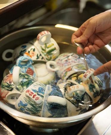 以熱水溫杯,讓端至客人前的咖啡溫熱適飲,杯身花色是蔡翠瑛以釉彩手繪上色。