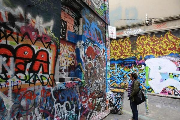 路人駐足觀賞一幅塗鴉,神情專注。