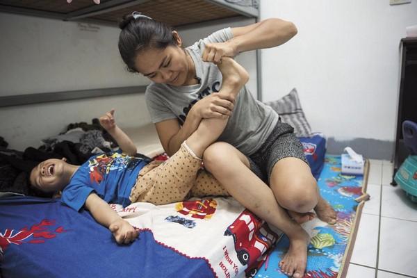 李沂每天幫腦傷兒典典拉筋復健,手腳因張力強而僵硬,撐開就會痛。