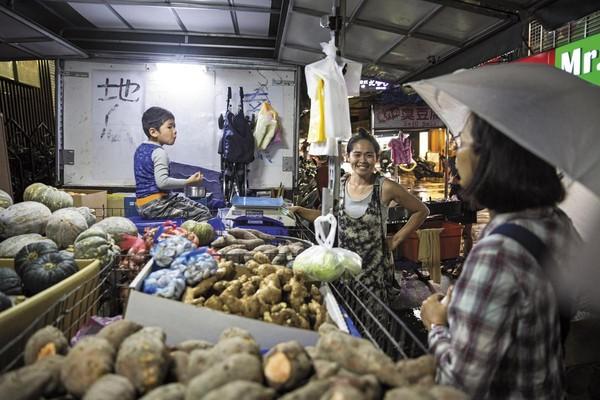 西湖市場附近許多熟客都支持帶著腦傷小孩而辛苦賣地瓜的李沂(中),還會給他們便當、麵包果腹。