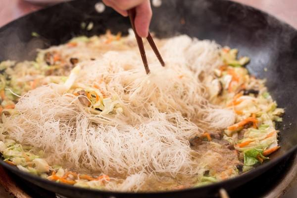 當含大量湯汁的配料煮滾後,再放入已沖濕的米粉,將湯汁配料與米粉拌炒均勻後即可上桌。