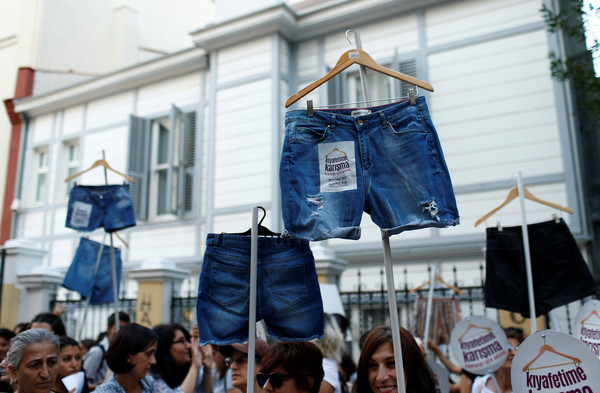 ▲示威者揮舞著「男性們覺得太暴露的牛仔短褲」          。(圖/路透社)