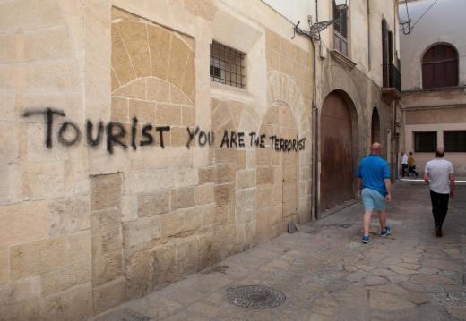 ▲▼ 西班牙旅遊業發達,但人民卻出現反彈聲浪,牆上的塗鴉寫著「遊客滾回家,只歡迎難民」。。(圖/路透社)