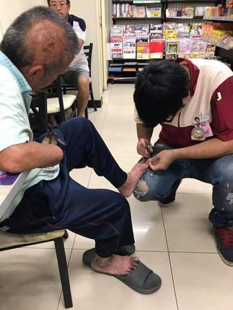▲小七店員蹲地...幫斷手老伯「剪腳趾甲」。(圖/翻攝自網友Yu Fei臉書,下同)