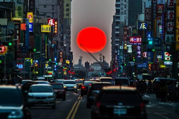 ▲高雄街頭的紐約曼哈頓「懸日」奇景。(圖/張忠義提供)