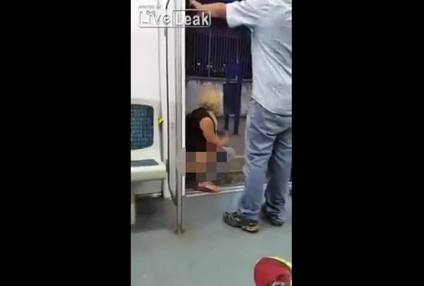 金髮女憋不住蹲月台電車間尿尿,尿完一臉舒爽坐回去。(圖/翻攝自Liveleak)