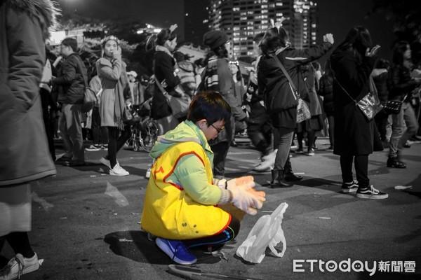 ▲▼跨年夜後的台北街頭,清潔人員默默上工,小男孩穿上志工背心,在人群中蹲下撿拾垃圾。(圖/網友陳家威授權提供)