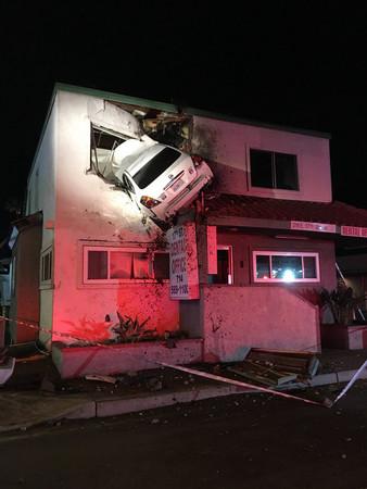 ▲▼加州的離奇車禍,車子撞上分隔島後飛天卡在二樓。(圖/達志影像/美聯社)