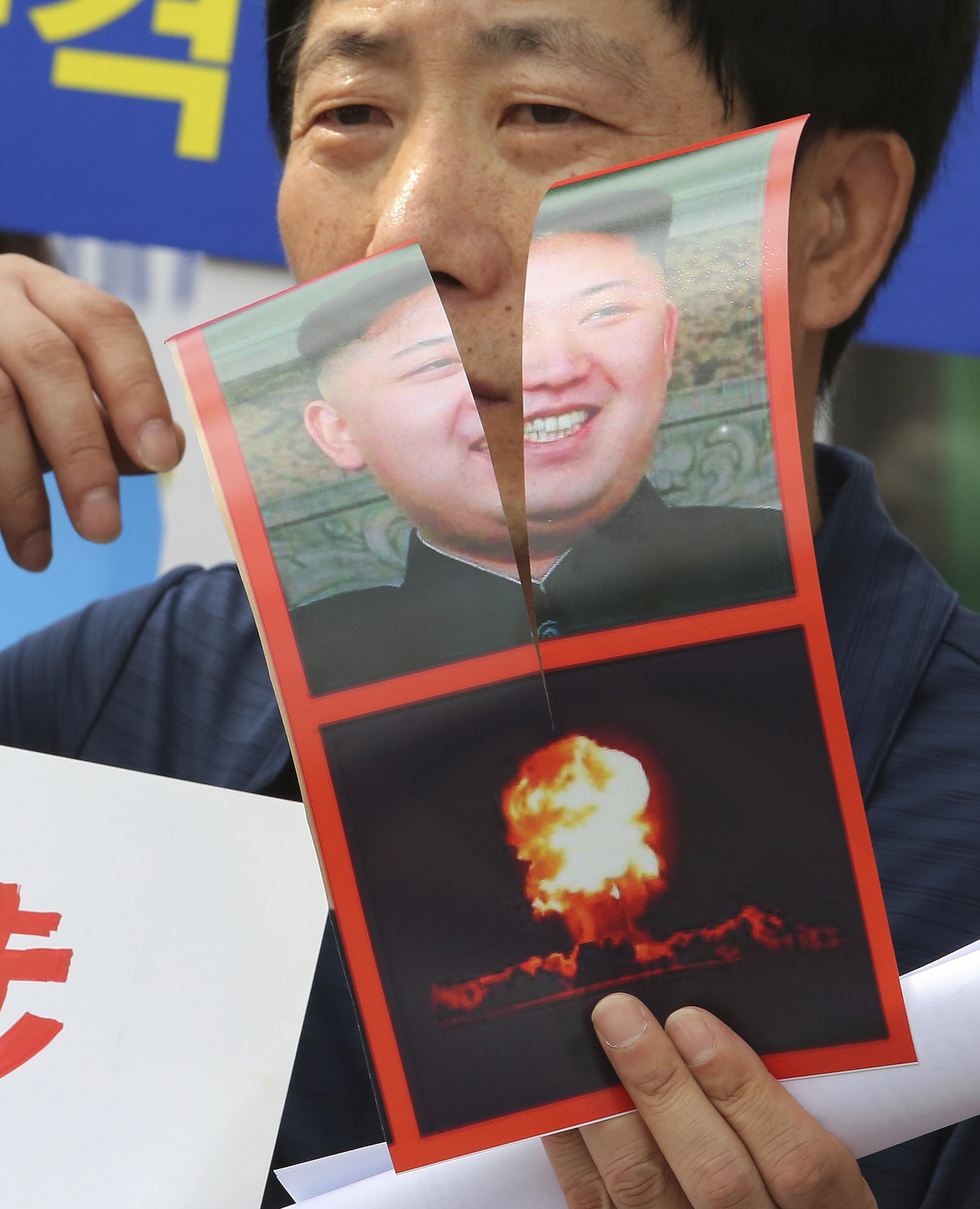 ▲▼脫北者朴尚學(Park Sang Hak)撕毀北韓領導人金正恩的海報。(圖/達志影像/美聯社)