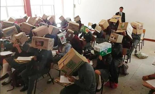 ▲墨西哥一位中學老師鐵西斯(右後方)為防止作弊,讓學(生們頭戴紙箱參加考試。(圖/翻攝自Mexico Daily News)