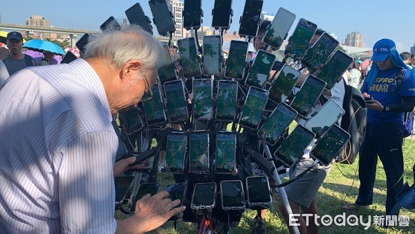▲朝聖!玩家爭相合照「寶可夢阿伯」 45支手機「孔雀開屏」成抓寶風景。(圖/記者姚惠茹攝)