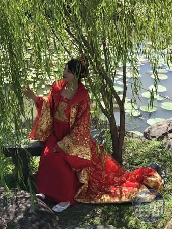 上原亞衣穿著大紅色古裝在樹下乘涼。(讀者提供)