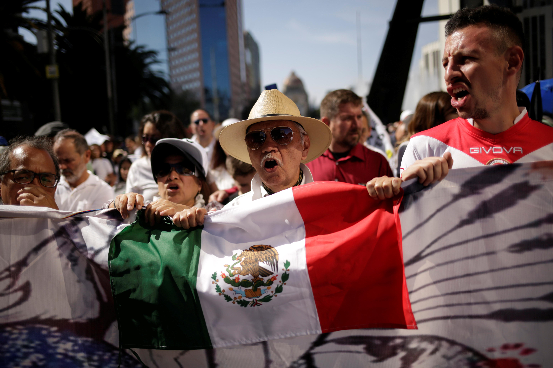 ▲▼墨西哥人民持國旗上街遊行,在總統羅培茲(Andres Manuel Lopez Obrador)上任滿一周年之際,發出「不要暴力」的怒吼。(圖/路透)