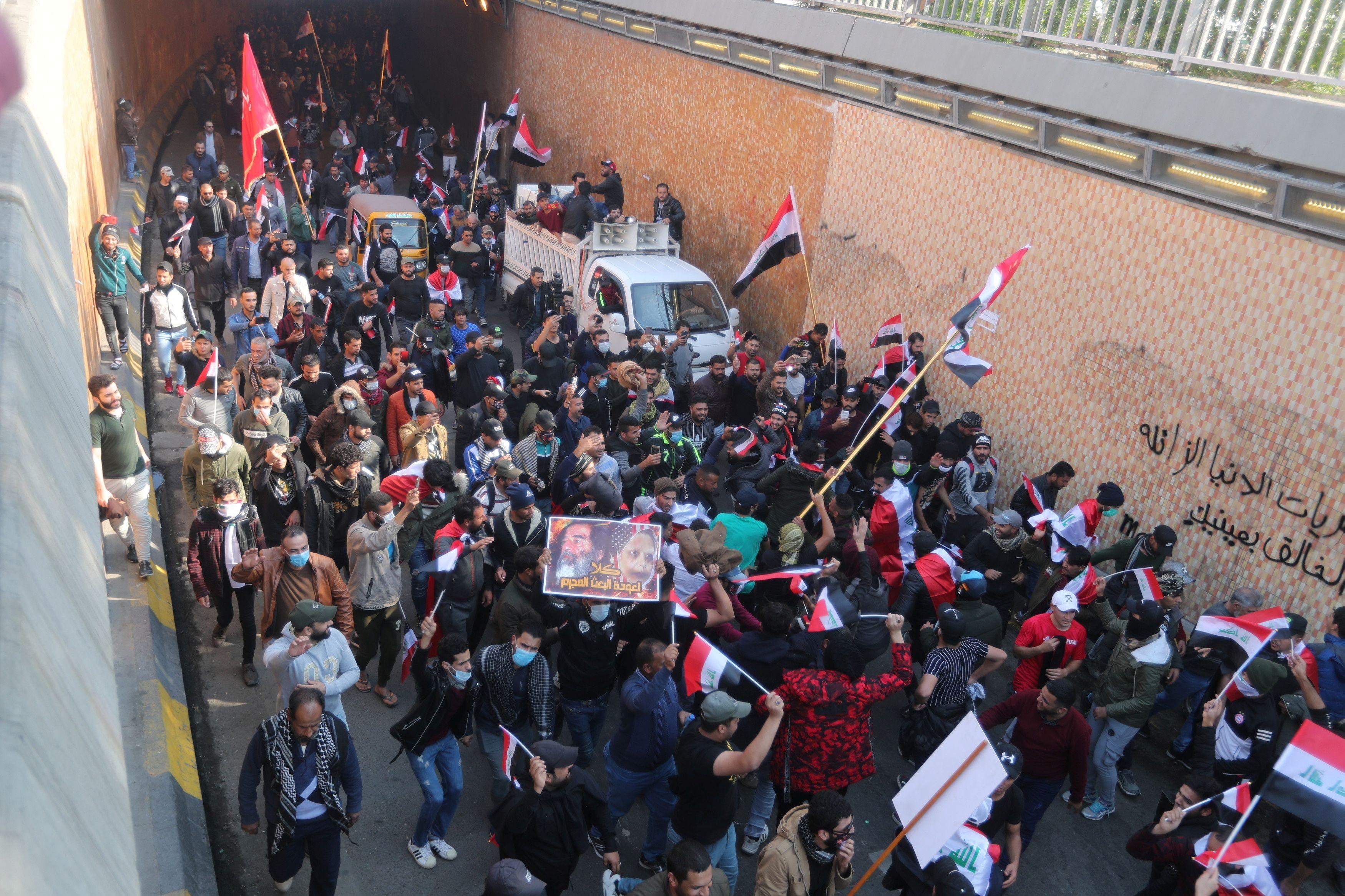 ▲▼伊拉克反政府示威至少440人死亡,示威民眾拿著亡者照片繼續遊行。(圖/路透)