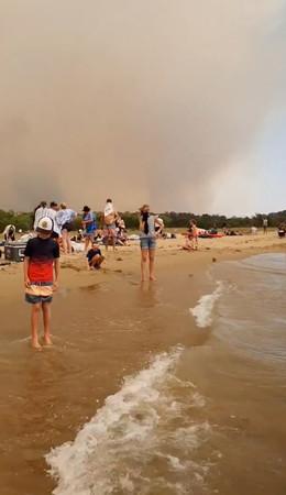 ▲澳洲野火肆虐,跨年人潮只能躲到海邊。(圖/路透社)