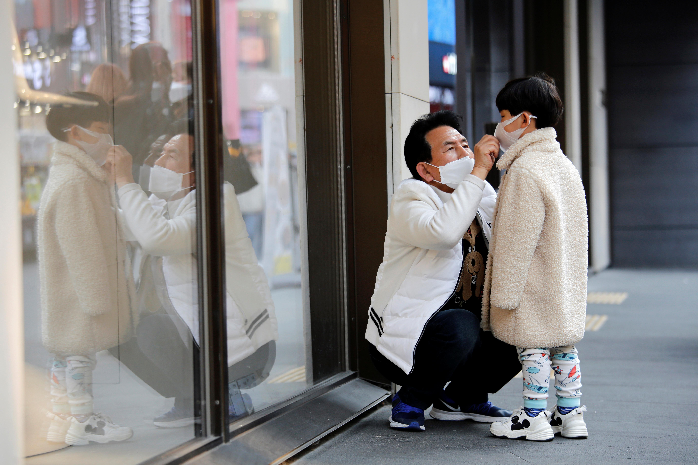 ▲▼首爾明洞一名男子為男童戴上口罩(圖/路透社)