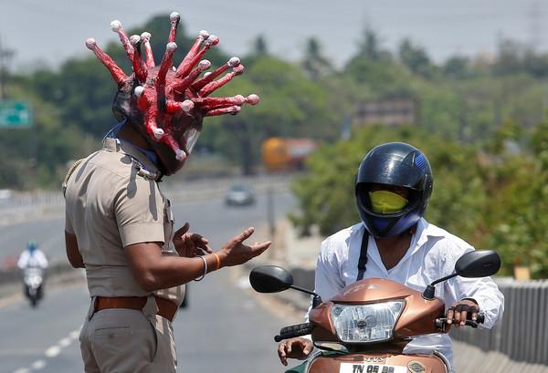 ▲▼印度下令封城,警察戴嚇人「新冠病毒頭盔」,要民眾不要出門。(圖/路透社)
