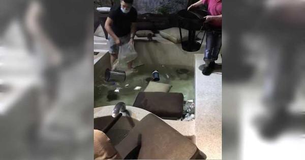 房間物品被大肆破壞,員工清理浴池內雜物。(圖/翻攝畫面)