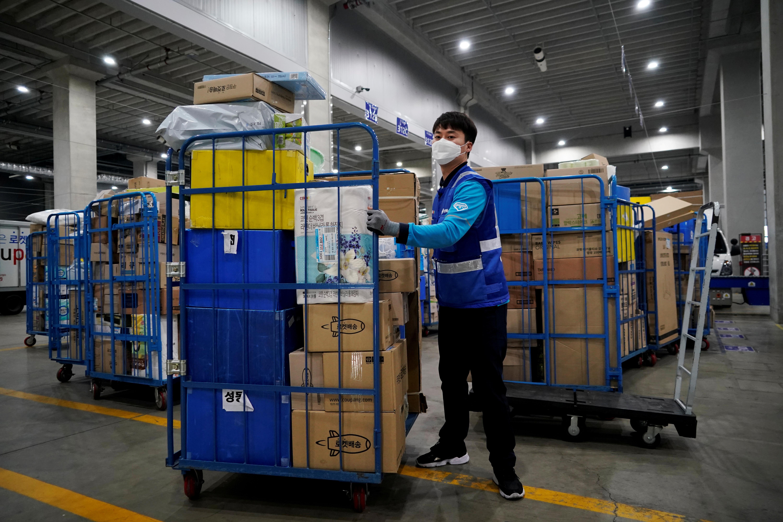 ▲▼南韓Coupang一名送貨員,在工作時配戴口罩。(圖/路透社)