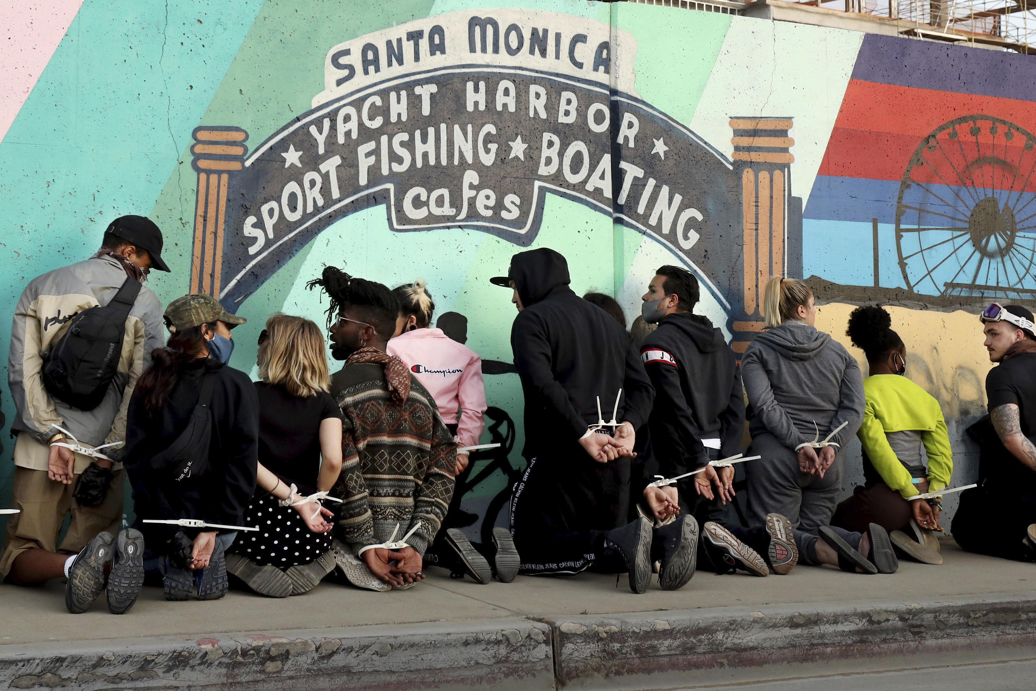 ▲▼美國聖莫尼卡抗議民眾遭警方逮捕,手綁起來一排靠在牆上(圖/達志影像/美聯社)