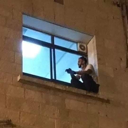▲▼一位勒斯坦孝子自母親確診後,每日爬上窗檯探病。(圖/翻攝自Twitter/mhdksafa)