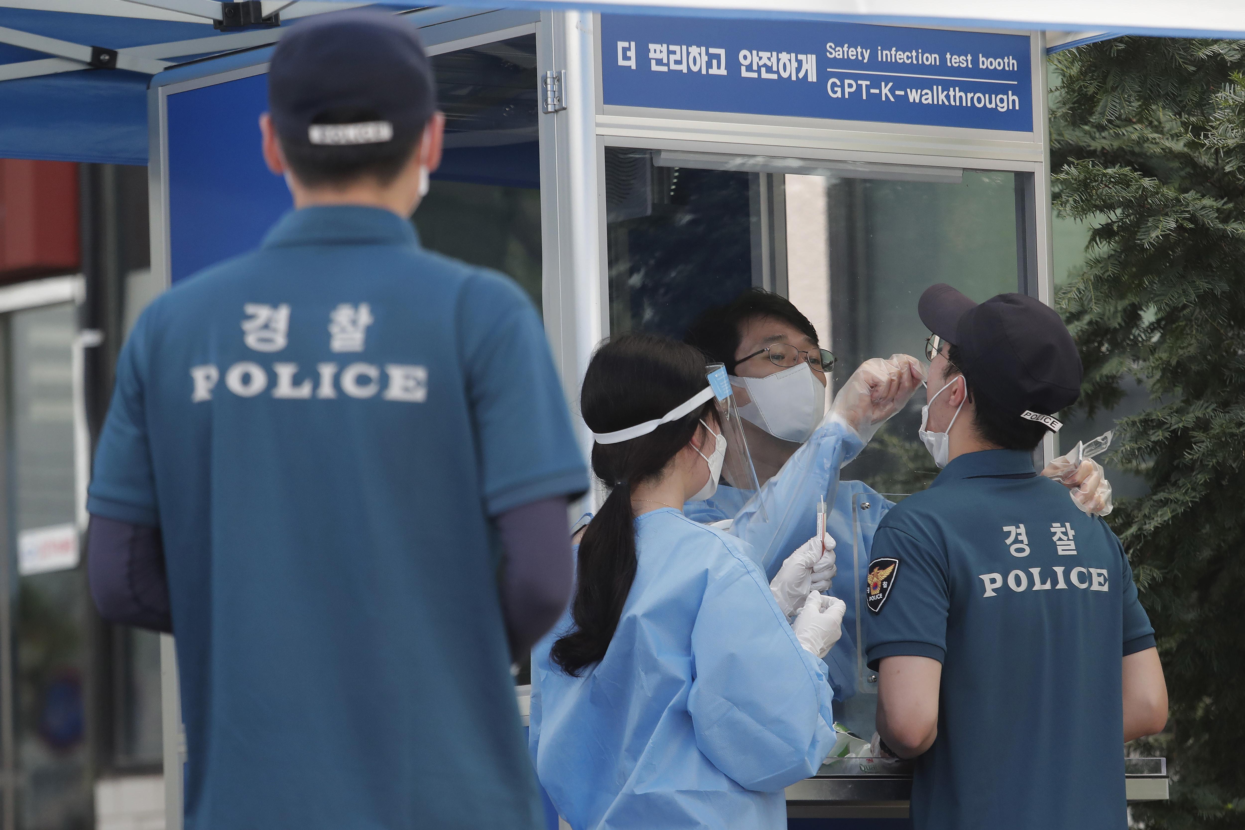 ▲▼醫護人員正為首爾市警察人員採樣篩檢。(圖/達志影像/美聯社)