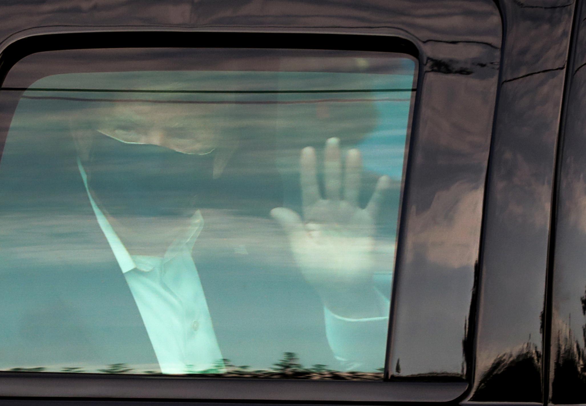 ▲▼川普坐車內向窗外支持者揮手致意。(圖/路透社)