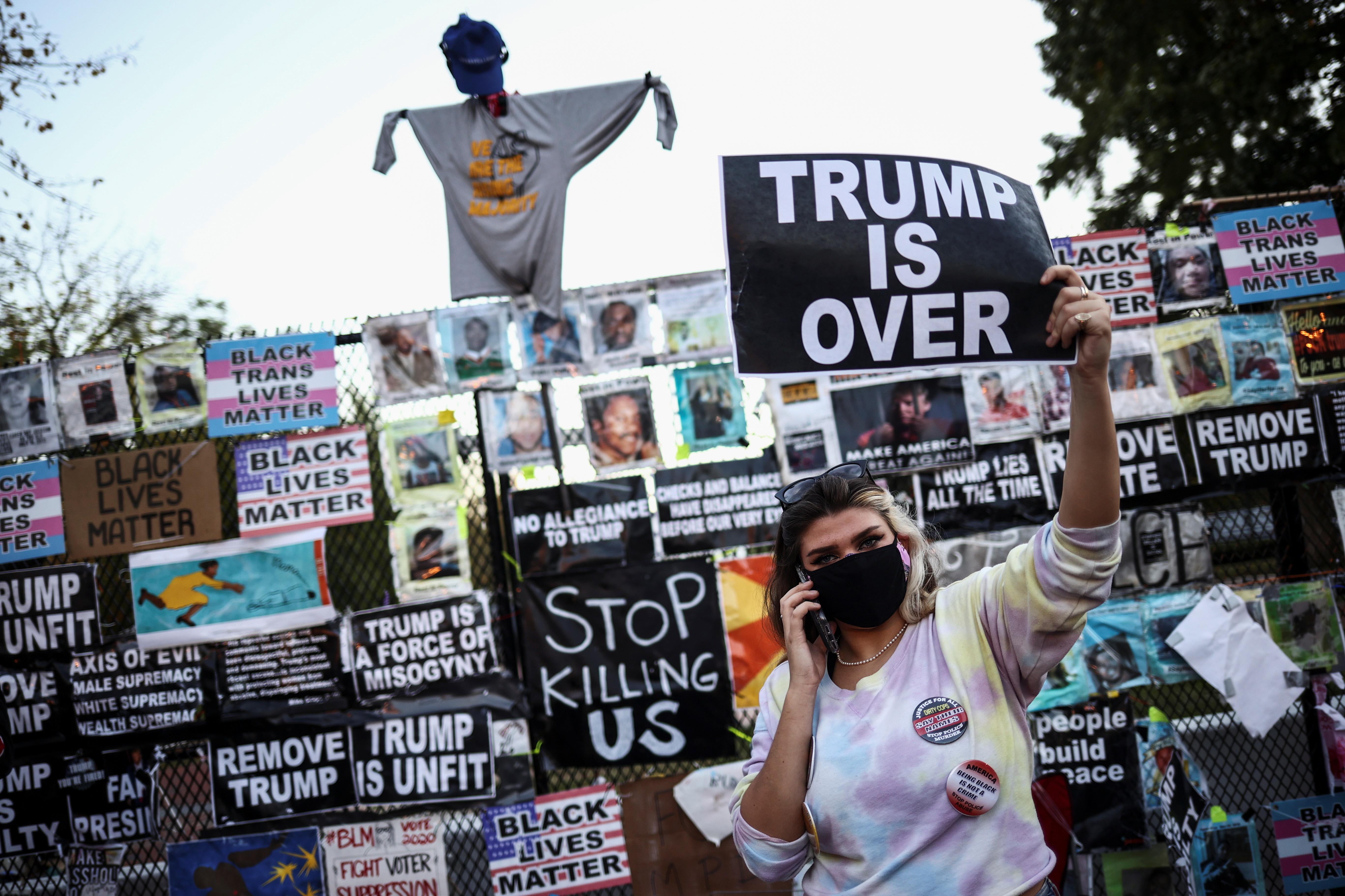 ▲▼拜登支持者在白宮前高舉標語,表示川普已經出局。(圖/路透社)