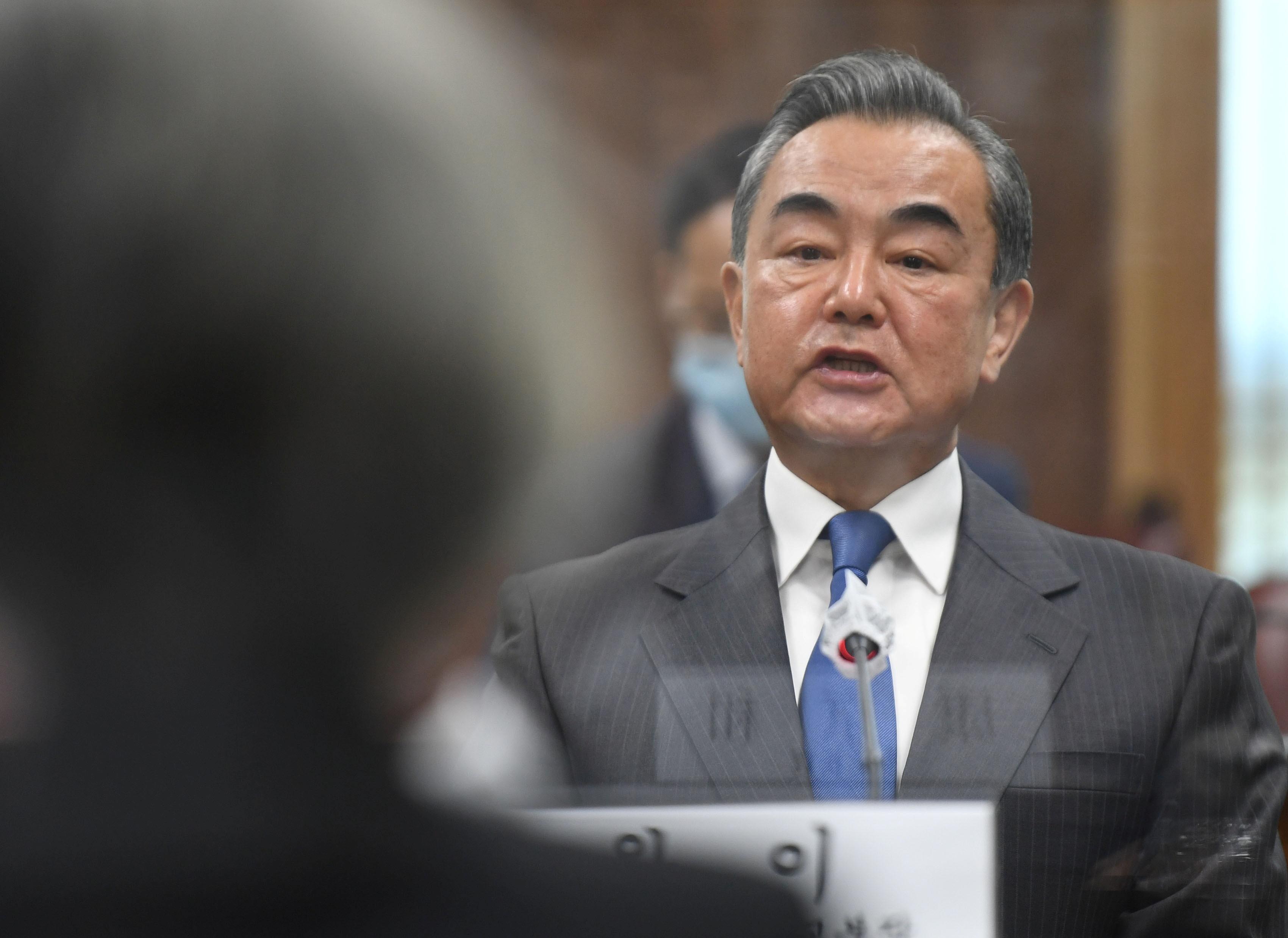 ▲▼王毅指著記者口罩表示,須等待南韓疫情穩定,才能推動習近平訪韓。(圖/路透社)