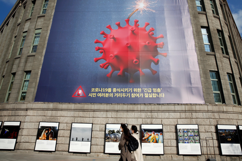▲▼首爾市府外牆貼上「緊急停止」海報,呼籲市民為防疫能減少不必要外出。(圖/路透社)