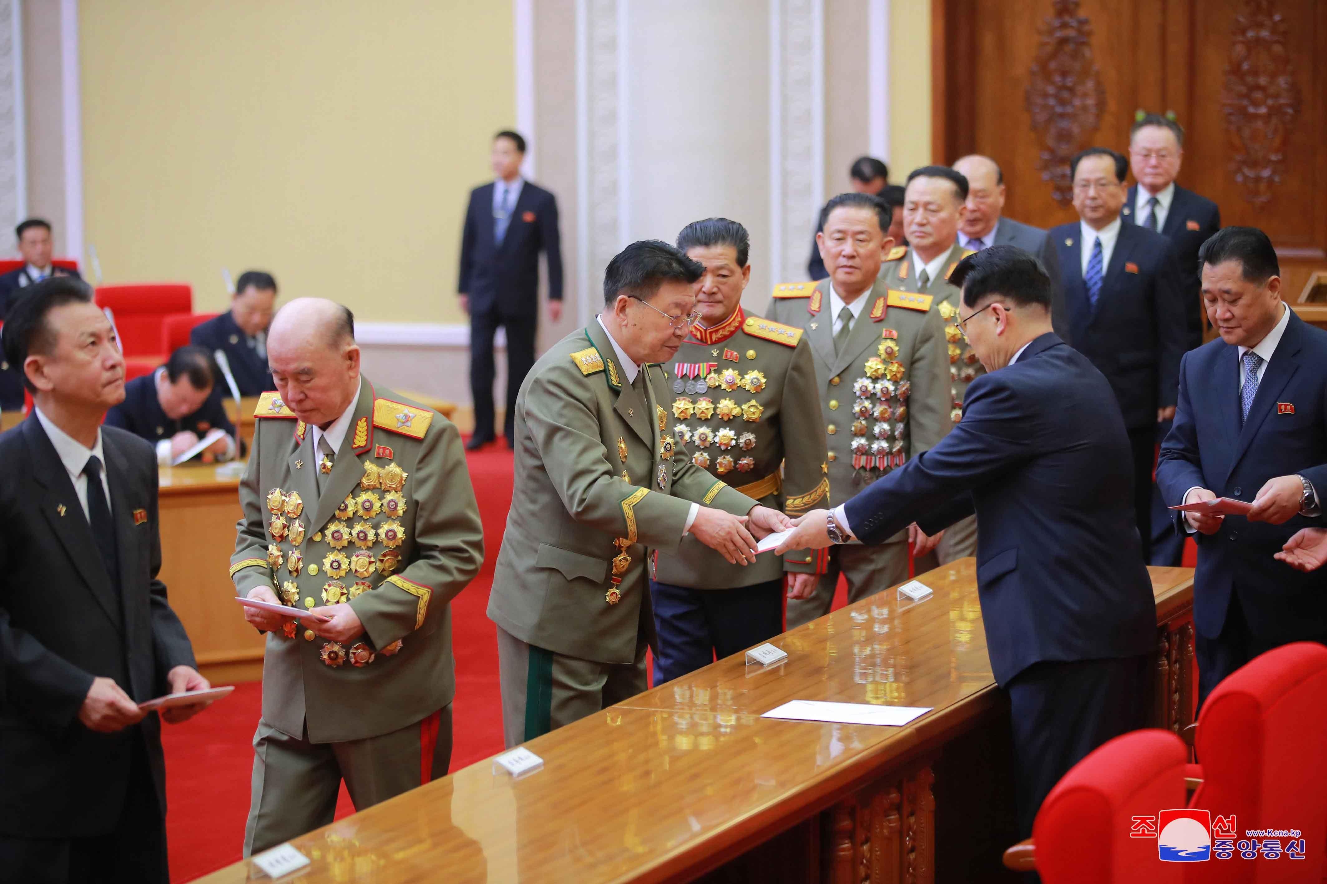 ▲▼北韓勞動黨副委員長金才龍授予各級黨代表第8次全代會代表證。(圖/達志影像)