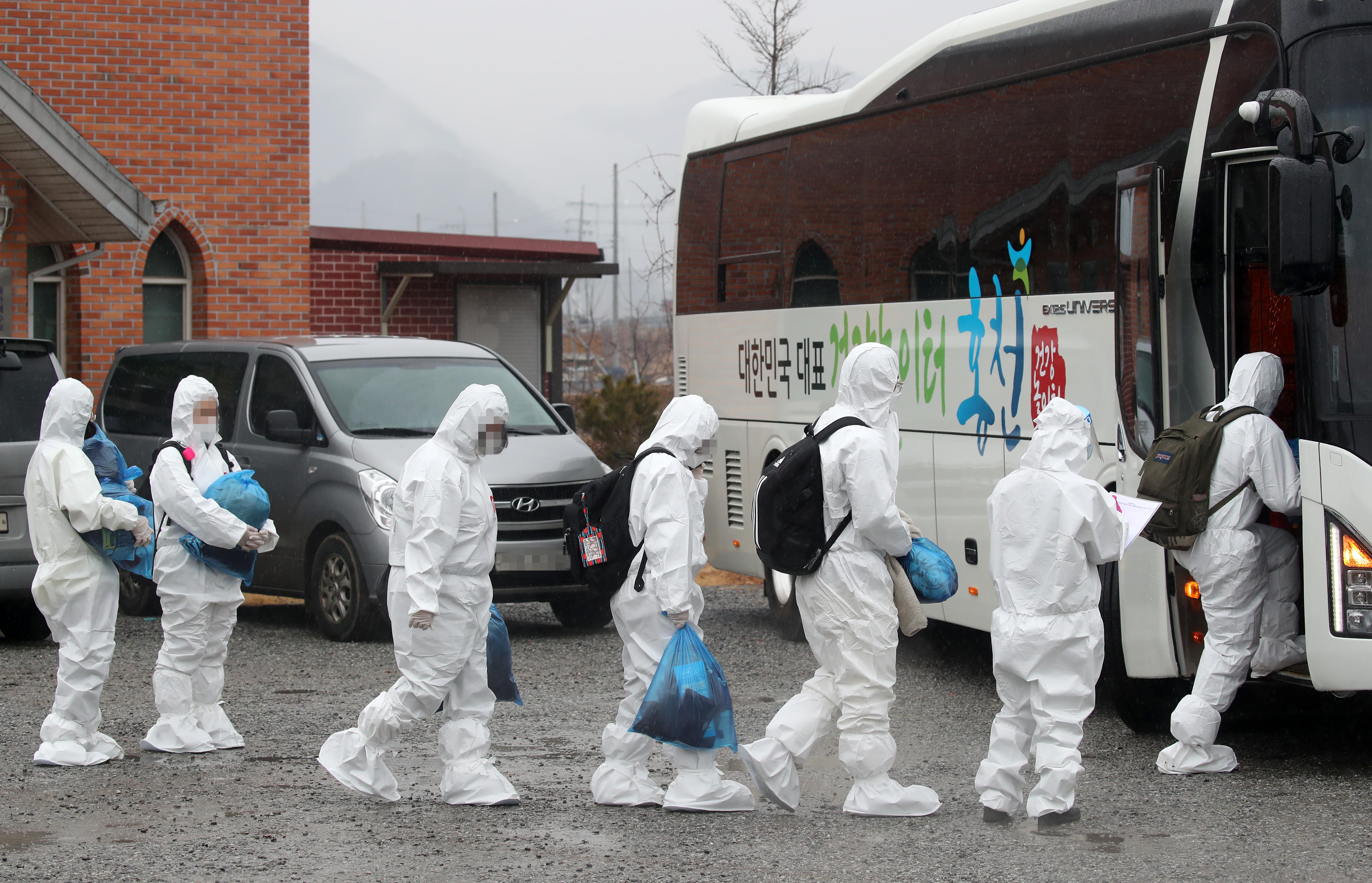 ▲▼南韓大田IEM國際學校爆發大規模感染,學生穿著防護衣前往診療所。(圖/達志影像)