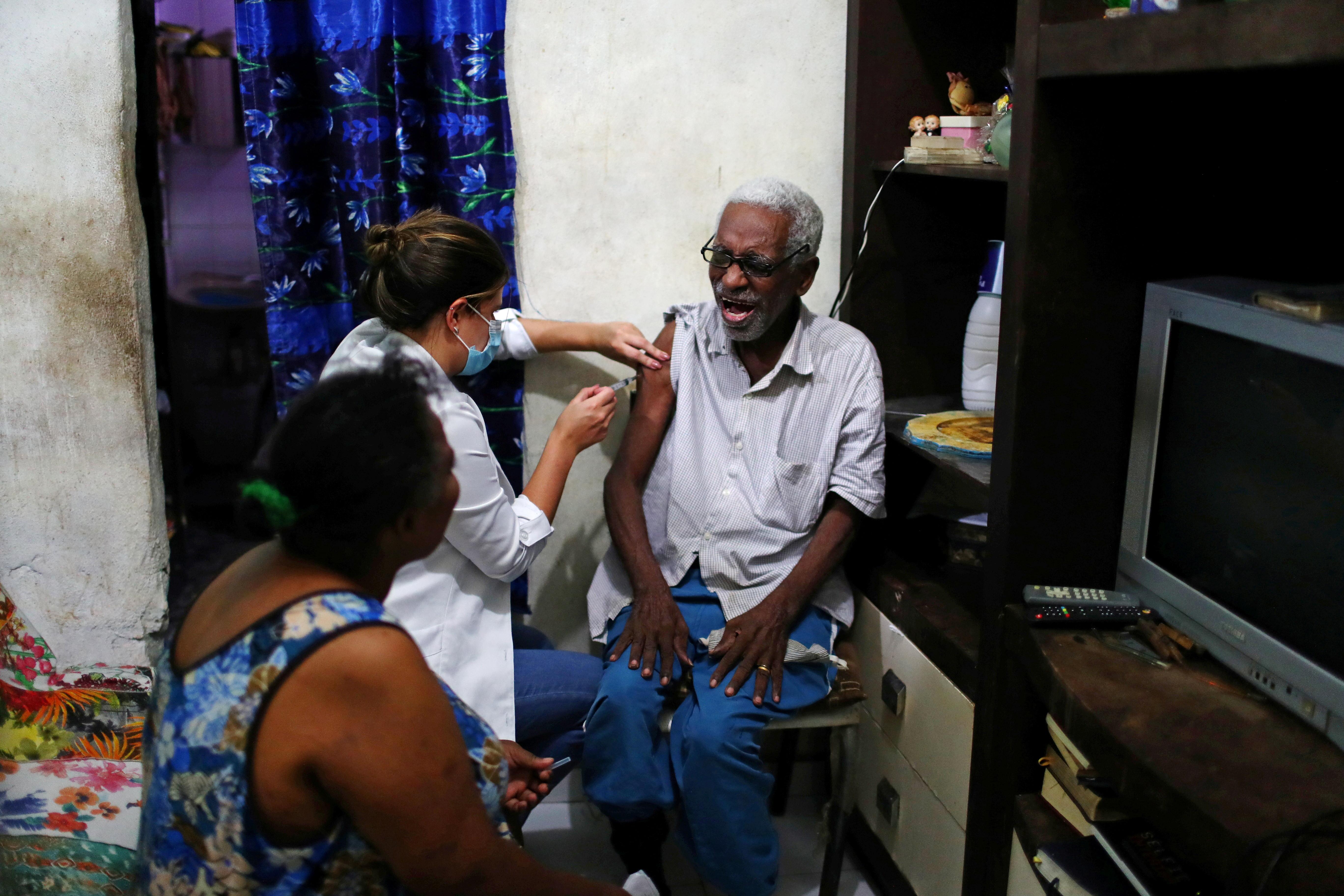 ▲▼巴西里約熱內盧一處貧民窟,醫護人員為男子施打新冠疫苗。(圖/路透社)