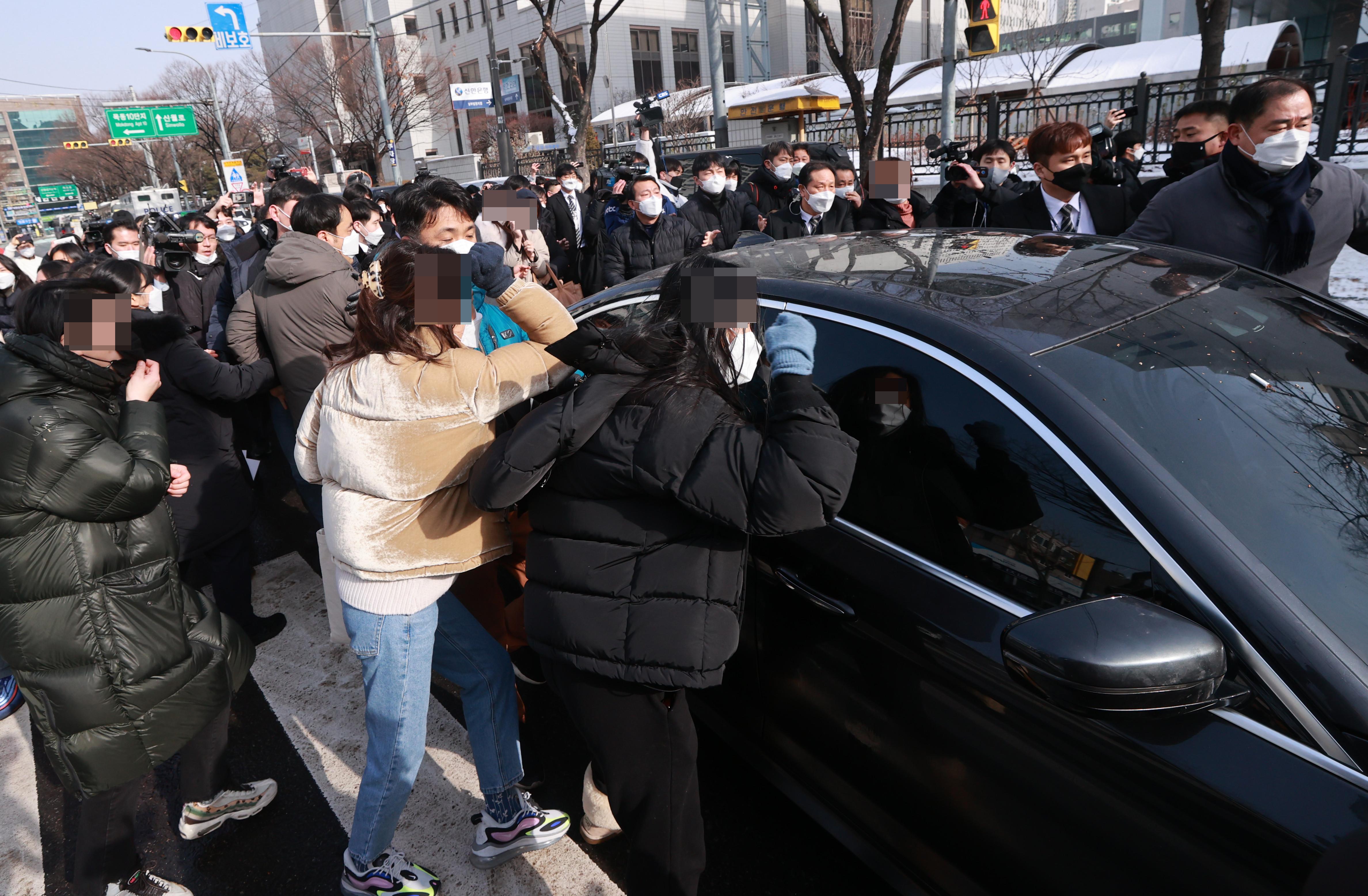 ▲▼民眾在首爾南部地方法院前,憤怒敲打鄭仁養父母車窗。(圖/達志影像)