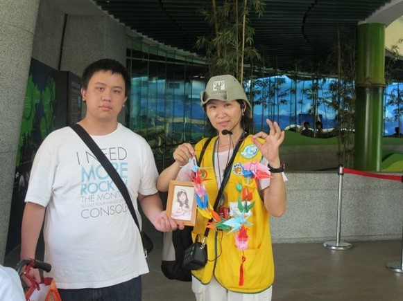 ▲ 動物園志工服勤與帶著妹妹遺照的哥哥合照。圖/朱寶貴 提供
