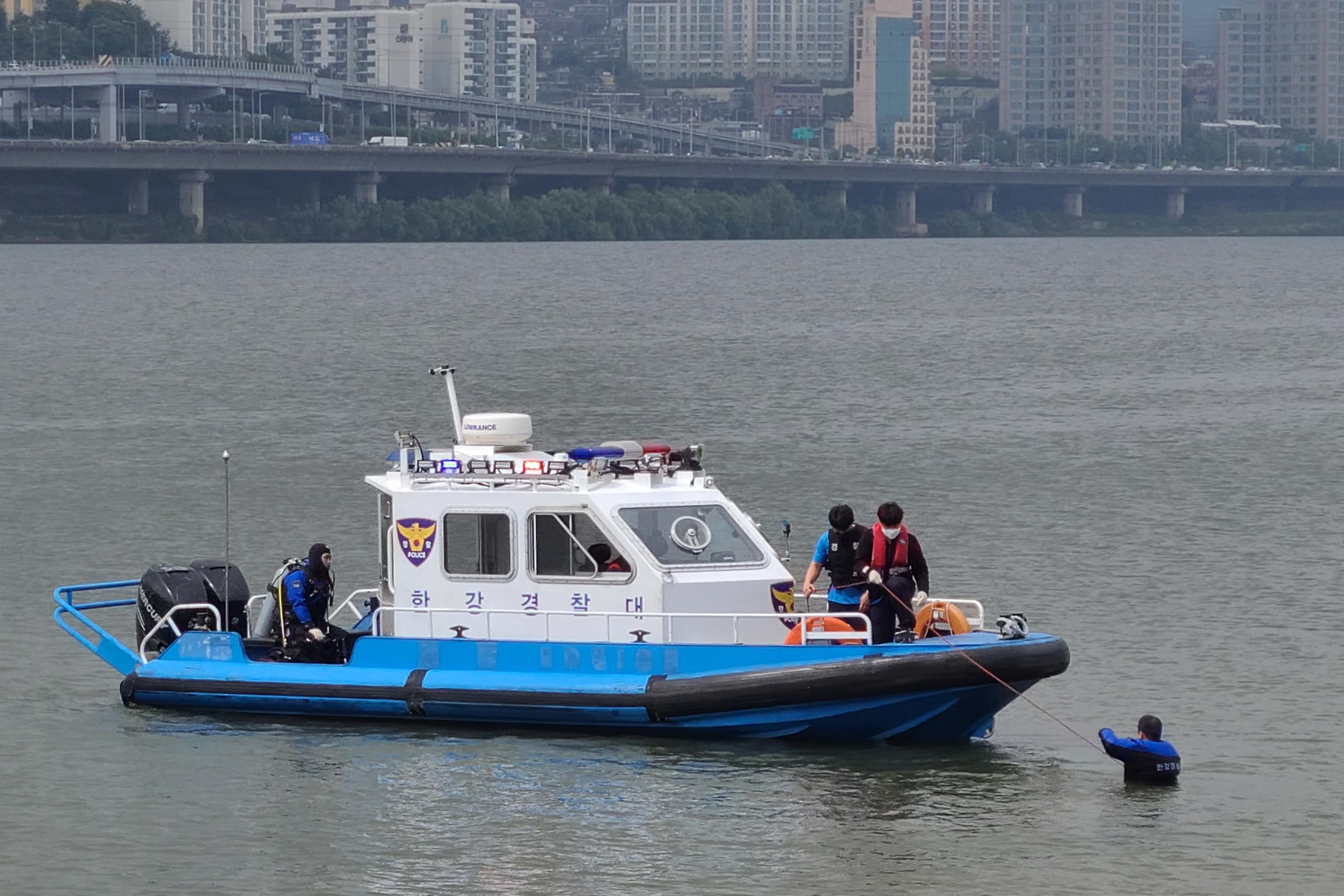 ▲▼孫正敏的屍體於4月30日在漢江上被搜救犬尋獲,調查人員探查水深,以求釐清死因。(圖/達志影像)
